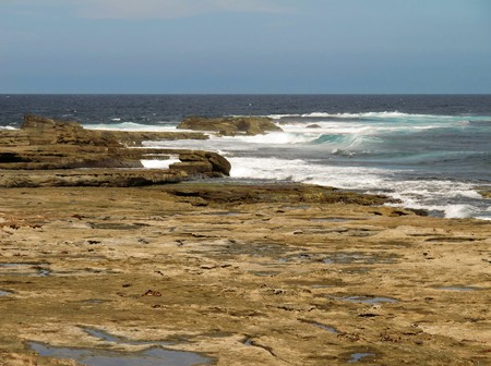 devonian: Tidal rock platform in australia with ocean in the background and neutral sky