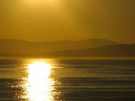 Sunset over the pacific with mountain range in background Stock Photo - 9513797
