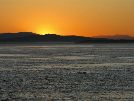 Sunset over the pacific with mountain range in background Standard-Bild