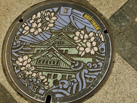 Manhole cover in Osaka, Japan showing the famous Osaka castle