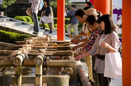 People washing hands at a Tsukubai in front of the Inari Shrine in Kyoto in order to purify themselves by the ritual washing