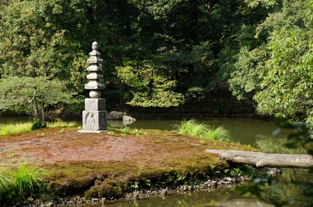 Japanese type of Buddhist pagoda on a island in the area of the Golden Temple in Kyoto, Japan photo