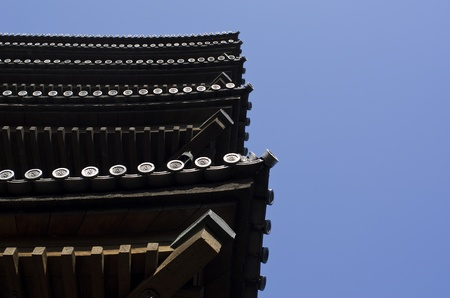storied: Edge of a five storied pagoda in Japan seen from below with blue sky background