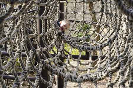 Young boy looking around the corner in a climbing net