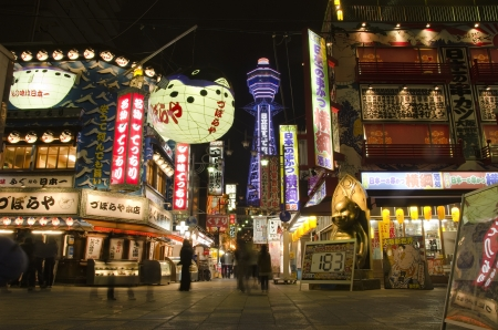 Tsutenkaku Tower in Shinsekai district at night, in Osaka, Japan with many restaurants