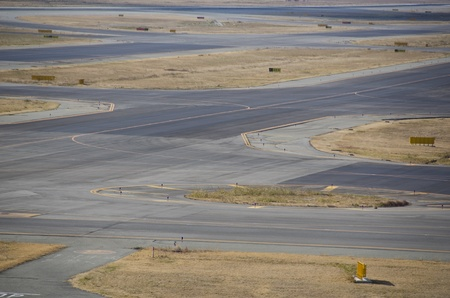 Detail of a runway at a airport with asphalt and grass photo