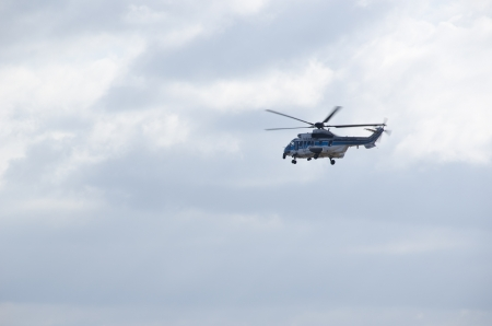 airpower: Japan Coast Guard Helicopter flying in front of a cloudy sky