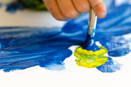 Child painting with an paint brush and water colors on paper