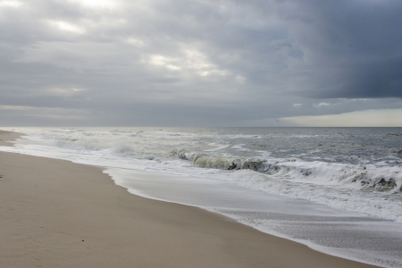 Beach with waves and gray rain clouds on a windy day