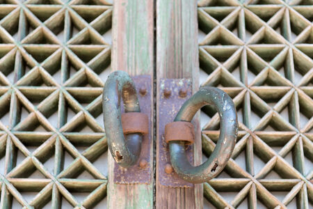 Detail of an old wooden door at a buddhist temple with door handles photo