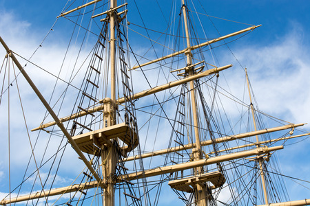 Masts and rigging of a big old sailing ship in front of a blue sky Stock Photo