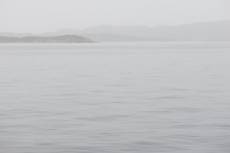 Seascape in Greenland on a foggy day with mountains, rain and calm water Stock Photo
