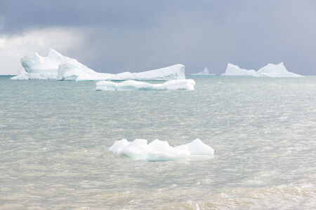 Beautiful icebergs in the sun and in front of a dark sky Stock Photo