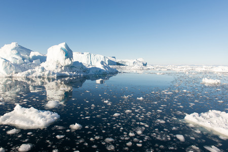 Arctic seascape in Greenland around Disko Island with icebergs and blue sky