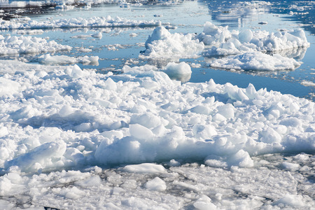icefjord: Floating Ice on the Ocean in Greenland with reflections of a blue sky in water