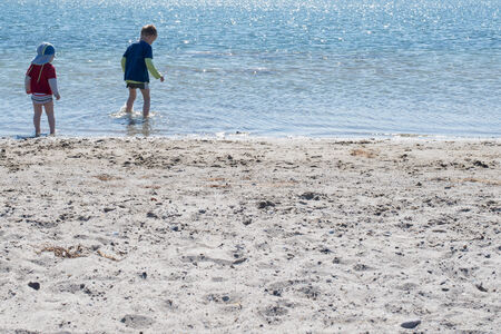 Sommer: Two kids playing on the beach in shallow water