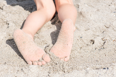 bare feet boys: Two feet of a boy in sand at at beach relaxing