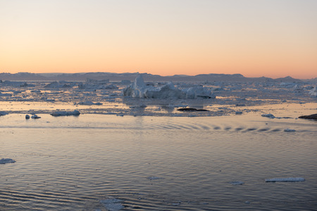Beautiful Icebergs in Disko Bay Greenland around Ilulissat with sky just after sunset