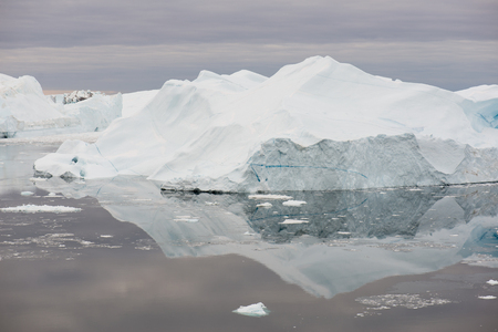 Arctic landscape in Greenland around Disko Island with icebergs, ocean, and cloudscape Stock Photo