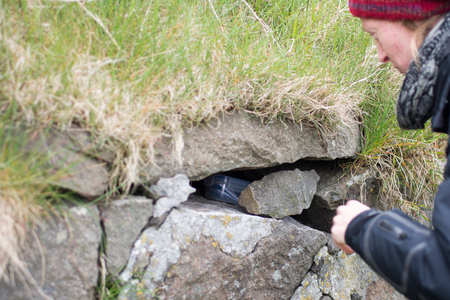 Young woman finding a geocache in a plastic box in a stone wall Stock Photo