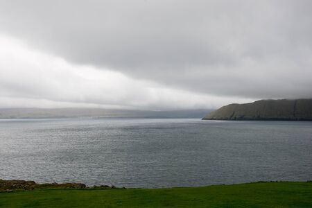 reisen: Typical landscape on the Faroe Islands as seen from Kirkjubour with green grass, mountains and sea