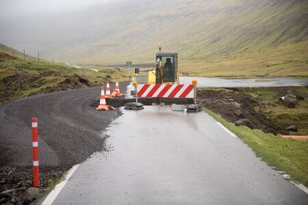 digger: Road construction site on the Faroe Islands with road block sign and digger Stock Photo