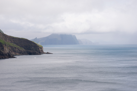 bleak: Typical landscape on the Faroe Islands as seen from Mykines with blue ocean and clouds Stock Photo