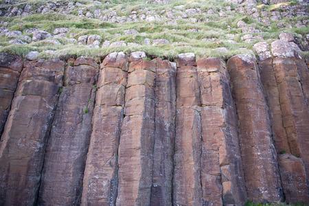 obrero: Grandes columnas de basalto rojo en Suduroy en las Islas Feroe