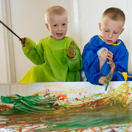 assiduous: Children painting with their hands on white paper on the floor