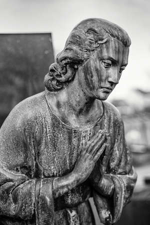 A statue of a saint praying intensely, photographed in black and white  Suggesting deep religious feelings and spirituality photo