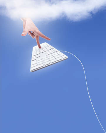 godlike: A godlike hand touching a flying keyboard from within the clouds Stock Photo