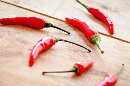 Arrangement of red  chilipeppers on a natural woorden background, photographed with a shallow depth of field