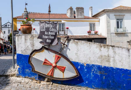 Obidos, Portugal - May 18, 2018: Sign pointing to a bar in the medieval town of Obidos, Portugal