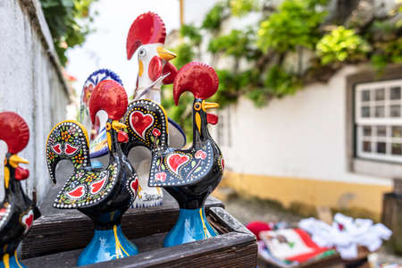 Obidos, Portugal - May 18, 2018: Rooster figurines in a tourist shop in the medieval town of Obidos, Portugal