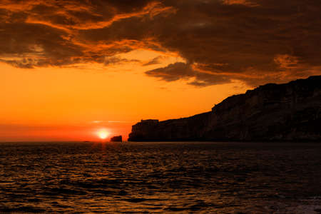 Nazare, Portugal - sunset over the lighthouse of Nazare