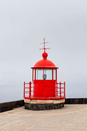 The red lighthouse lamp room on top of the Farol of Nazare in the mist Banco de Imagens