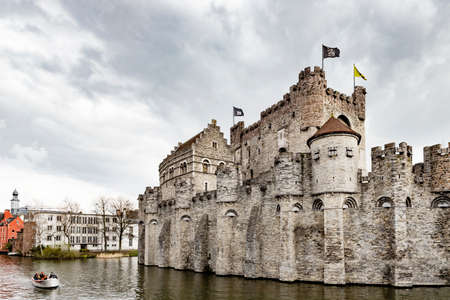 Ghent, Belgium - March 28, 2019:  A boat filled with tourists passes the famous Gravensteen or the Castle of the Counts.