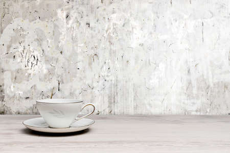 Vintage teacup on a white wooden table, textured wall