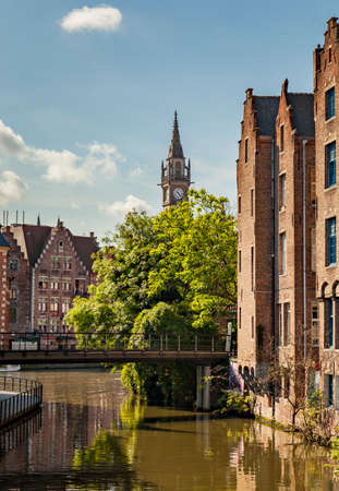 The clock tower of the old postal building with of the canals in the foreground