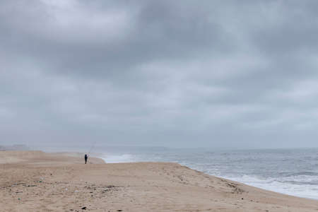 Nazare, Portugal - Lonely fisherman on the north beach