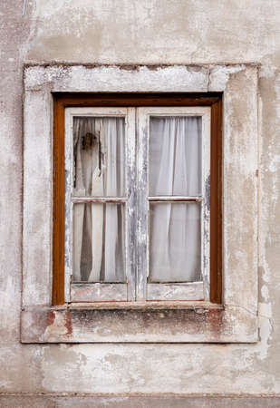 Nazare, Portugal - An old broken window in an abandoned house