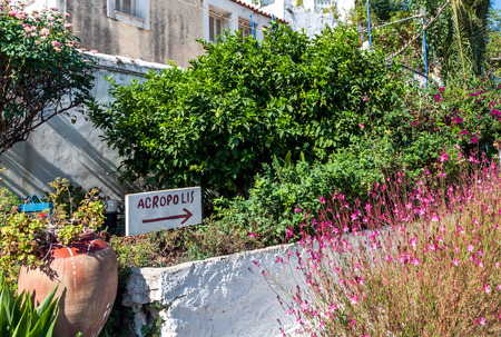 The old handmade signpost standing beetween garden flowers and pointing to the Acropolis in Athens, Greece