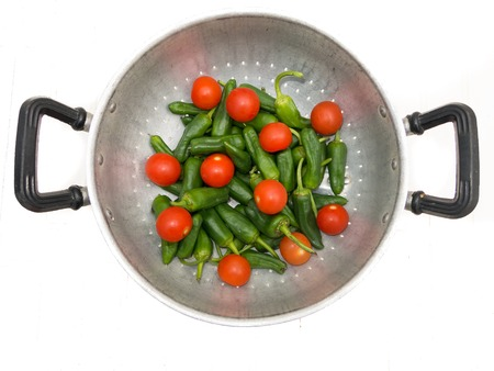 Green peppers and tomatoes in the metal bowl photo