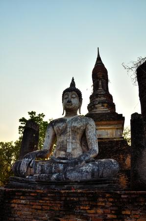 buliding: Photo of buddha sitting in front of ruin pagoda at  Sukhothai Historical Park, Thailand  Stock Photo