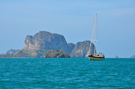 Photo of sailboat lie at anchor in the middle of the ocean  Behind is the moutains and the beach  This photo take at Krabi, Thailand   photo