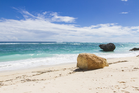 Lonely stone on white sand beach