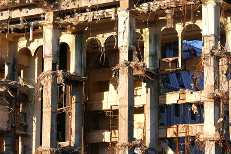 Demolished destructed building ruins. Demolition site in european city. Ruined house on a bright blue sky at sunset Imagens