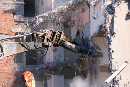 Building demolition with hydraulic excavator close-up. Demolished destructed house ruins in european city on bright sunny day.