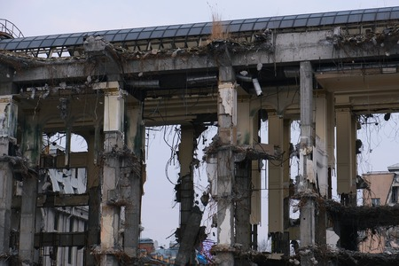 Demolished destructed building ruins. Demolition site in european city. Ruined house on a gray sky on cloudy day