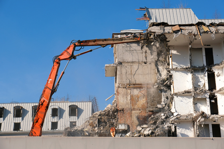 Building demolition with hydraulic excavator. Demolished destructed house ruins in european city on bright sunny day.